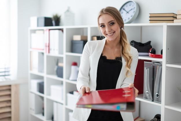 Uma jovem garota fica no escritório ao lado do rack e estende uma pasta vermelha com documentos.