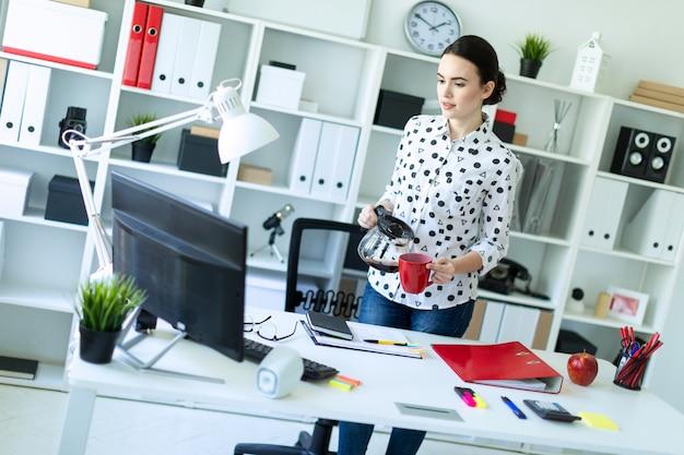 Uma jovem garota fica no escritório perto da mesa e derrama café da cafeteira em um copo vermelho.