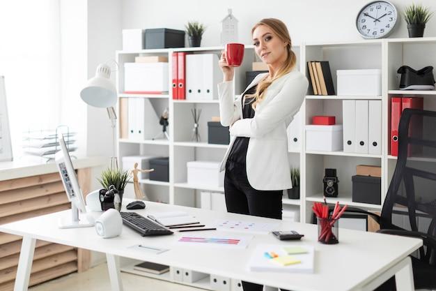 Uma jovem garota fica no escritório perto de uma mesa de computador e detém um copo vermelho nas mãos dela.