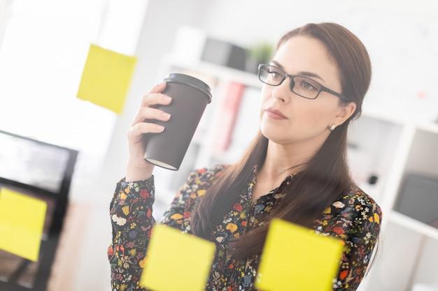 Uma jovem garota fica no escritório perto de uma placa transparente com adesivos e bebe café.