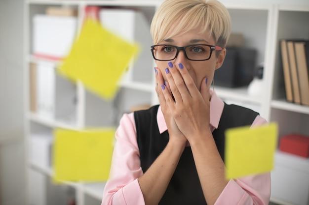 Uma jovem garota fica no escritório perto de uma placa transparente com adesivos e cobriu a boca com as mãos.