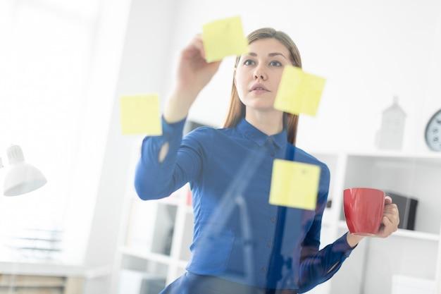 Uma jovem garota fica no escritório perto de uma placa transparente com adesivos e segura um copo vermelho nas mãos.