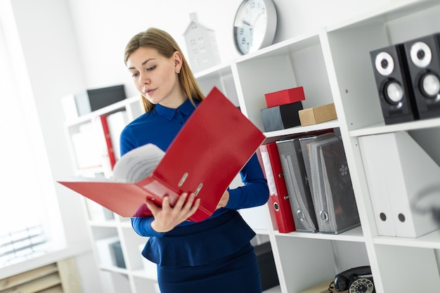 Uma jovem garota fica no escritório perto do abrigo e detém uma pasta com documentos em suas mãos.