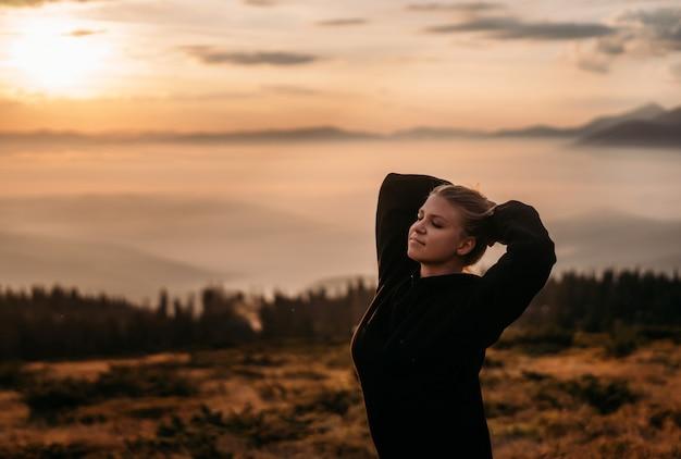 Uma jovem garota fica no topo de uma montanha, mãos atrás da cabeça e sorri em paz. vista lateral. amanhecer nas montanhas. a atmosfera acolhedora da foto. paz interior. facilidade de mente. o equilíbrio na vida.