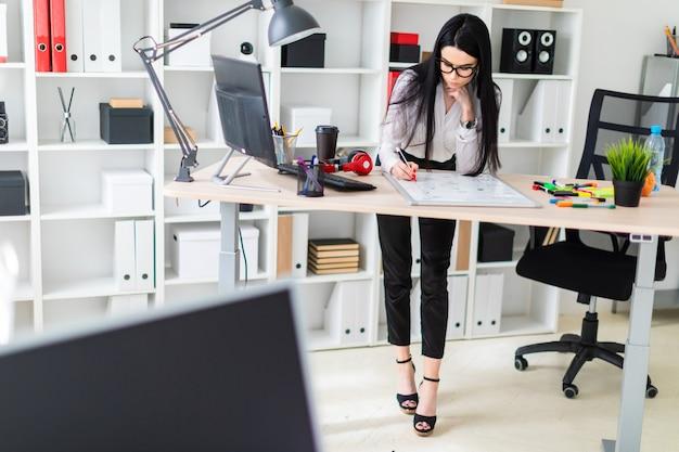 Uma jovem garota fica perto de uma mesa de computador e desenha um marcador em uma placa magnética.