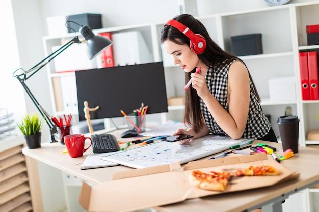 Uma jovem garota fica perto de uma mesa e detém um marcador e um telefone nas mãos dela.