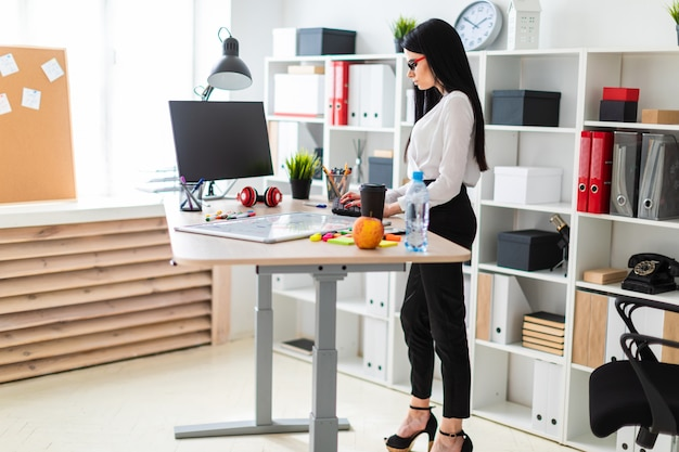 Uma jovem garota fica perto de uma mesa e imprime no teclado. antes que a menina é um quadro magnético e marcadores.