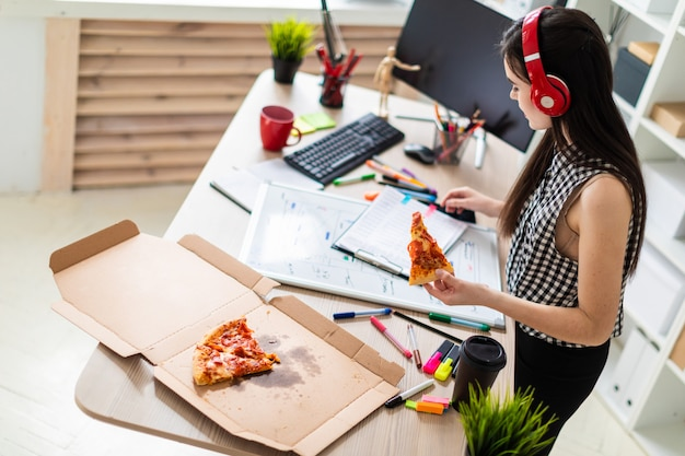 Uma jovem garota fica perto de uma mesa e tem um pedaço de pizza na mão. antes da menina em cima da mesa há um quadro magnético.