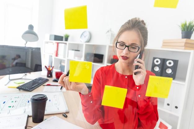 Uma jovem garota fica perto de uma placa transparente com adesivos e detém um marcador e um telefone.
