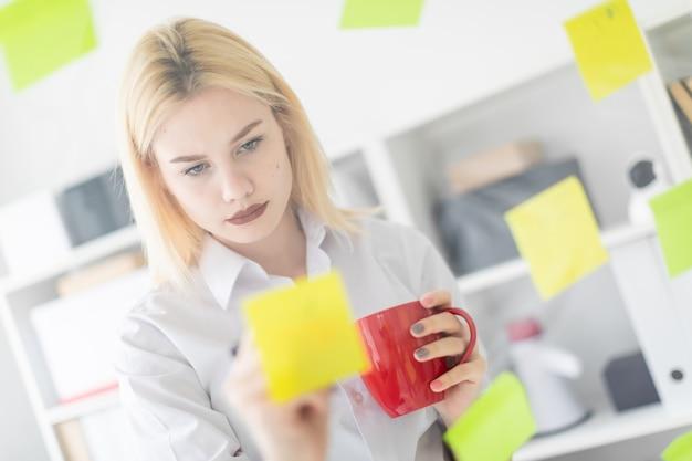Uma jovem garota fica perto de uma placa transparente com adesivos. ela está segurando uma xícara e um marcador.