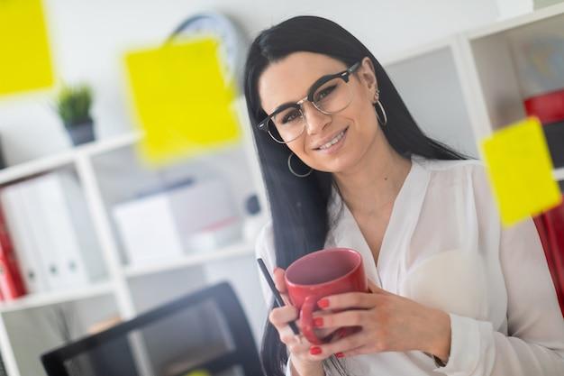 Uma jovem garota fica perto do quadro com adesivos e tem um copo vermelho e lápis nas mãos dela.