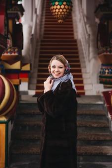 Uma jovem garota linda com um casaco de vison e um cachecol folclórico russo anda pelo kremlin de izmailovo. moscou, rússia.