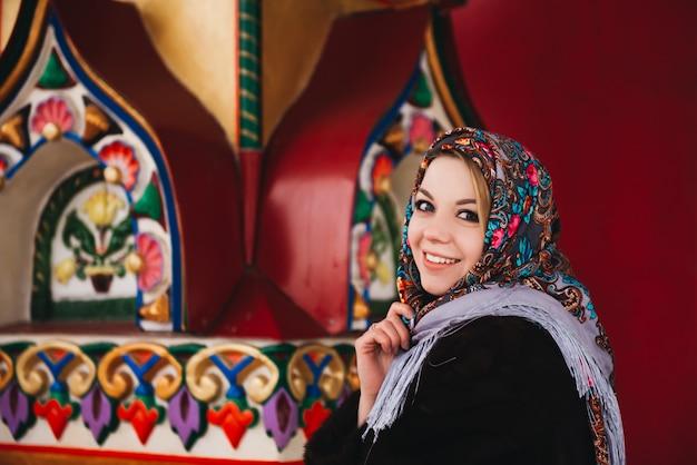 Uma jovem garota linda com um casaco de vison e um cachecol folclórico russo anda por moscou