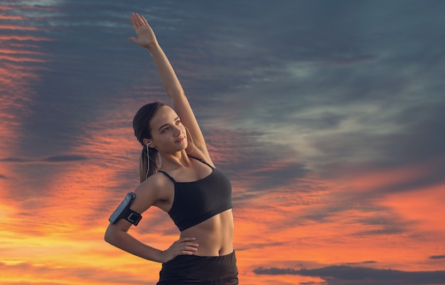 Uma jovem garota magra e atlética em roupas esportivas com estampas de pele de cobra realiza uma série de exercícios