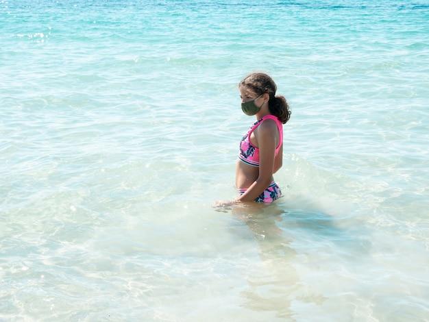 Uma jovem garota na praia usando uma máscara protetora para prevenir a doença de coronavírus