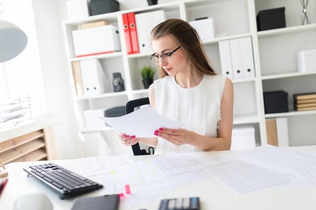 Uma jovem garota no escritório está segurando um lençol.