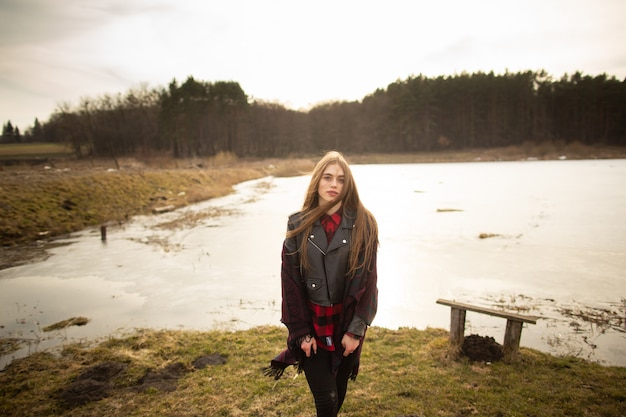 Uma jovem garota posa na margem de um lago