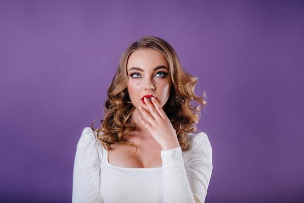 Uma jovem garota posando no estúdio com parede roxa