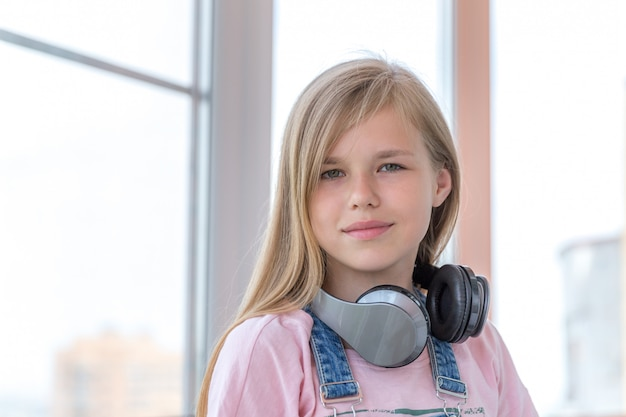 Uma jovem garota que gosta de ouvir música no fone de ouvido com tablet