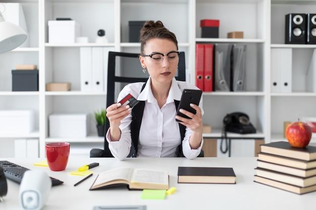Uma jovem garota se senta em uma mesa de computador no escritório e possui um cartão e telefone bancário.