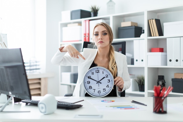 Uma jovem garota se senta em uma mesa no escritório e aponta um dedo para o mostrador do relógio.