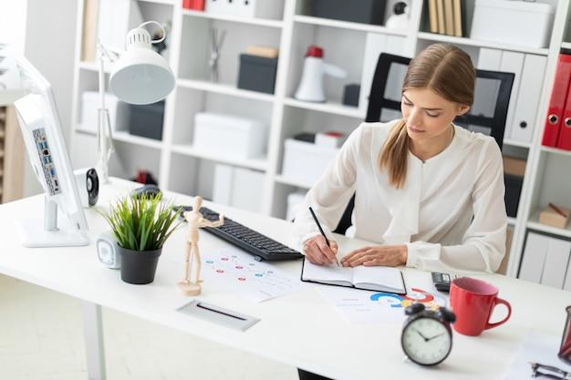 Uma jovem garota se senta em uma mesa no escritório e escreve com um lápis em um caderno.