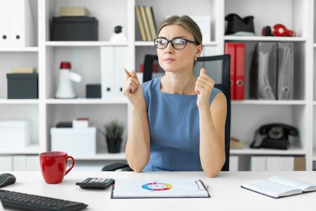 Uma jovem garota se senta em uma mesa no escritório e olha para um documento com um gráfico.