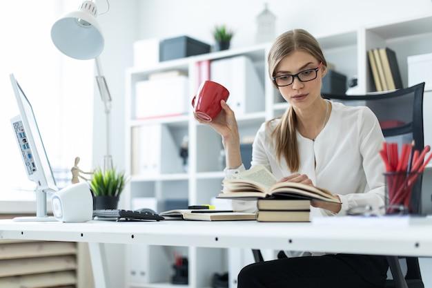 Uma jovem garota se senta em uma mesa no escritório e tem um copo vermelho na mão e lê um livro.