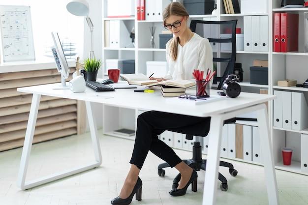 Uma jovem garota se senta em uma mesa no escritório e tem um lápis na mão. antes que a menina jaz um livro aberto.