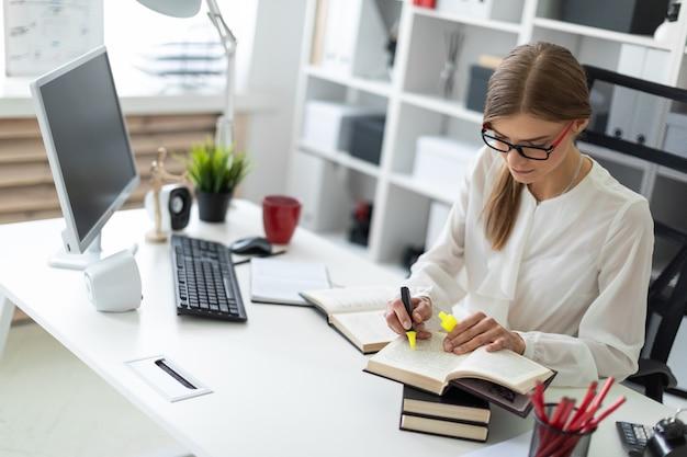 Uma jovem garota se senta em uma mesa no escritório e tem um marcador amarelo na mão. antes que a menina jaz um livro aberto.