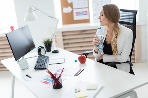 Uma jovem garota se senta em uma mesa no escritório e tem uma garrafa de água na mão. antes que a menina em cima da mesa seja uma maçã.