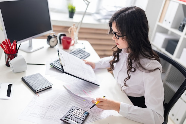 Uma jovem garota se senta na mesa do escritório e verifica os documentos.