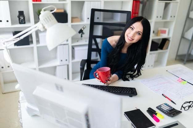 Uma jovem garota se senta no escritório à mesa e tem um copo vermelho nas mãos.
