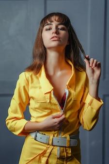 Uma jovem garota sedutora em uma roupa desabotoada amarela