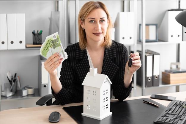 Uma jovem garota segurando o dinheiro e as chaves. diante dela, em cima da mesa, está o layout da casa.