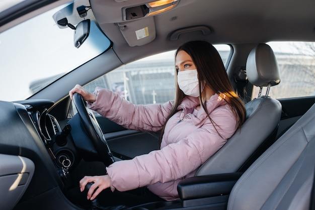 Uma jovem garota senta-se ao volante do carro na máscara durante a pandemia global e o coronavírus. quarentena.