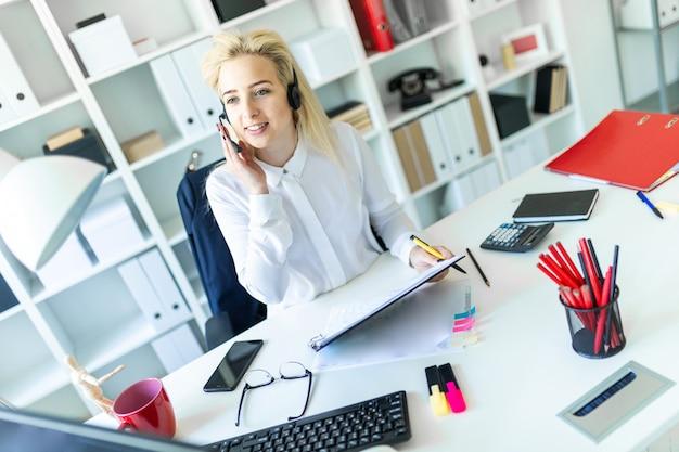 Uma jovem garota senta-se em fones de ouvido com um microfone na mesa do escritório e faz anotações no documento.
