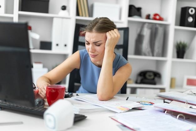 Uma jovem garota senta-se no escritório em uma mesa de computador e apóia a mão na cabeça dela.