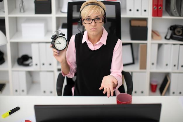 Uma jovem garota sentada em uma mesa de computador e segurando um despertador.