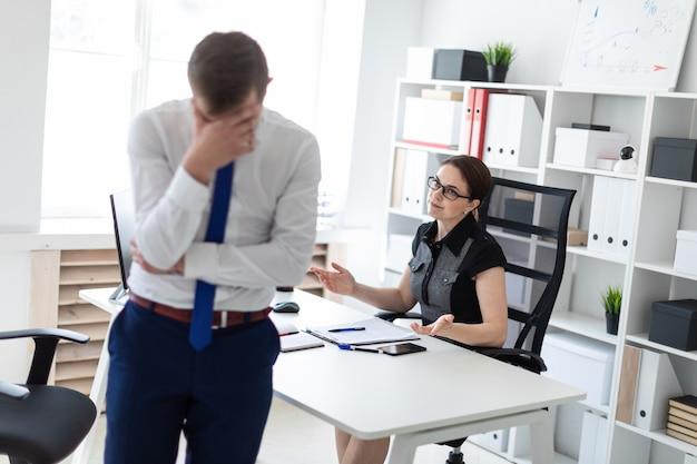 Uma jovem garota sentada no escritório à mesa do computador. ao lado dela está um jovem.