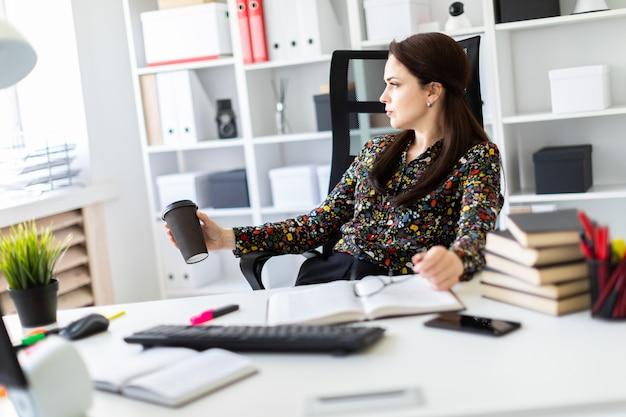 Uma jovem garota sentada no escritório à mesa do computador e segurando um copo de café.