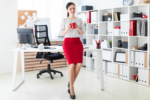 Uma jovem garota sentou-se em uma mesa de computador no escritório e segurando uma taça vermelha.