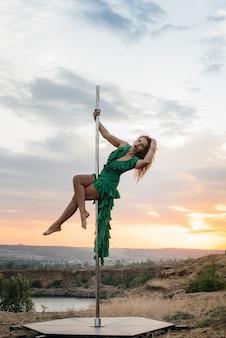 Uma jovem garota sexy realiza exercícios incríveis em um poste durante um belo pôr do sol. dança. sexualidade.
