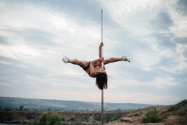 Uma jovem garota sexy realiza exercícios incríveis em um poste durante um belo pôr do sol.