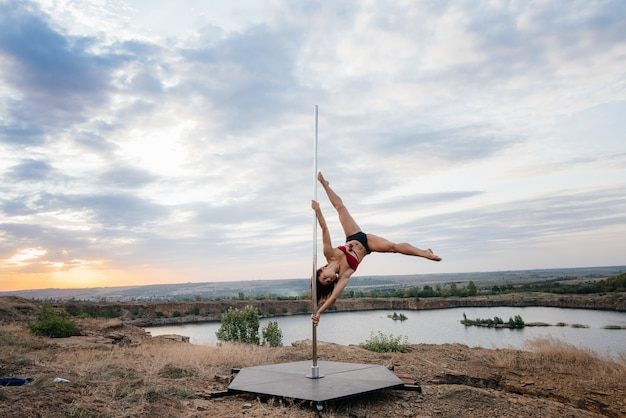 Uma jovem garota sexy realiza exercícios incríveis na pole durante um belo pôr do sol. dança. sexualidade.