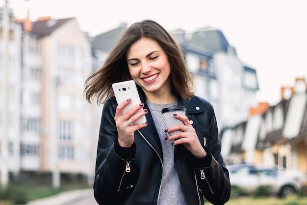 Uma jovem garota sorri e caminha pela cidade com um telefone celular e uma xícara de café