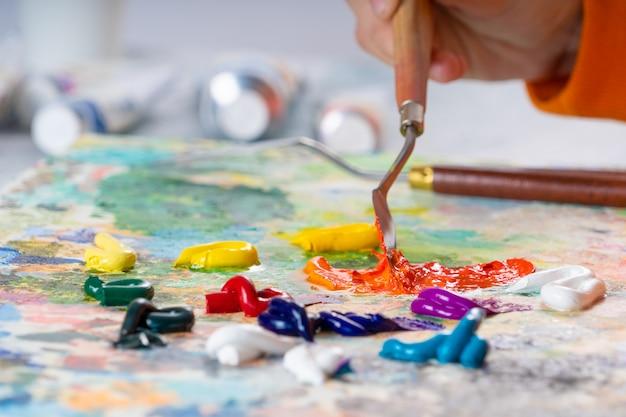 Uma jovem garota tem em sua mão uma paleta de facas para desenhar e mistura tintas oleadas.