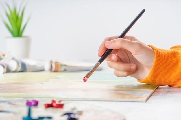 Uma jovem garota tem um pincel na mão e enterra na pintura a óleo.