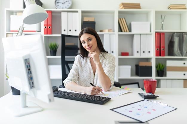 Uma jovem garota trabalhando no escritório com documentos e um computador.