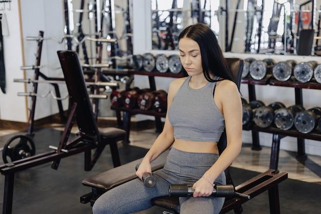 Uma jovem garota vestindo roupas esportivas em um ginásio realiza exercícios com halteres, o treinador ajuda ela
